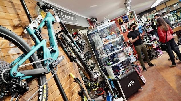 Un vélo accroché au mur alors que des clients sont conseillés.