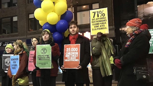 Des gens alignés sur le trottoir avec des pancartes.