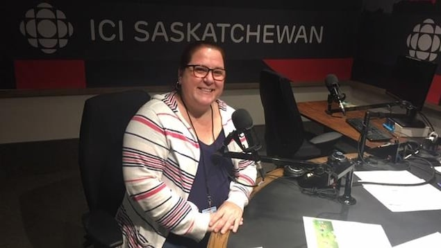 Une femme sourit devant la caméra dans le studio de Radio-Canada Saskatchewan