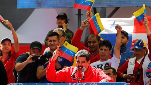 Un homme portant une chemise noire gesticule en parlant derrière deux micros lors d'un rassemblement avec des personnes brandissant des drapeaux du Venezuela.