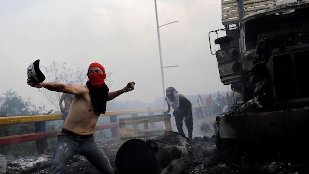 Un homme, torse nu et masqué, s'étire pour lancer un projectile à côté d'un camion incendié.