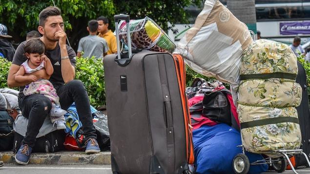 Un jeune homme pensif assis sur une valise tient une fillette qui pleure dans ses bras.