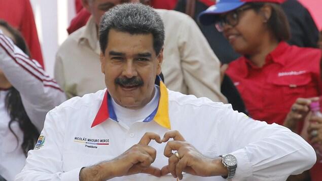 Nicolas Maduro forme un signe de coeur sur sa poitrine avec ses mains.