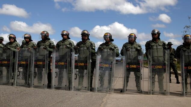 Casqués et armés de boucliers, des soldats vénézuéliens se tiennent en rangée bloquant une route.