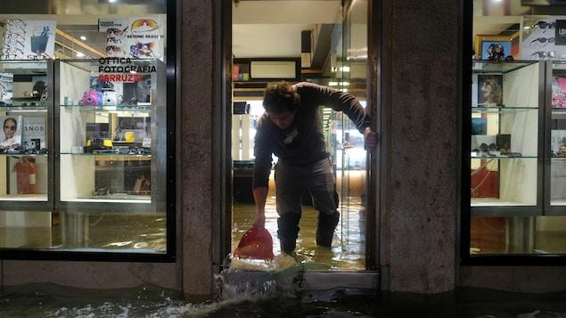 Un homme utilise un contenant pour jeter de l'eau à l'extérieur de son commerce, qui est inondé.