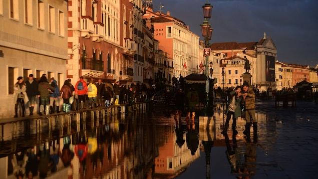 Des touristes marchent dans des rues inondées de Venise au coucher du soleil.