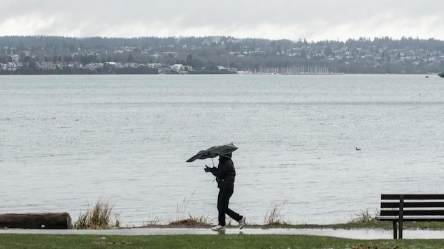 Une personne marche sur le bord de l'eau avec un parapluie soufflé par le vent.