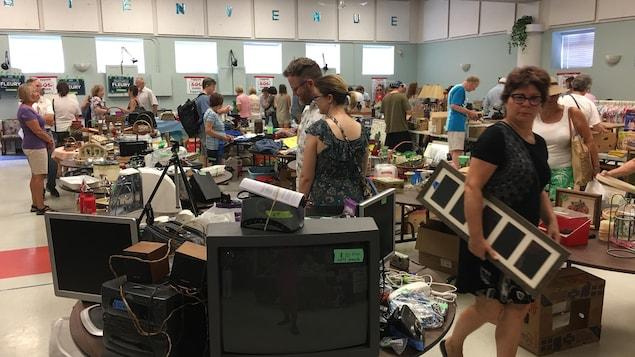 Des gens regardent diverses marchandises disposées sur des tables dans une salle communautaire lors d'une grande vente de garage.