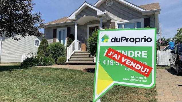 Une pancarte de vente devant une maison.