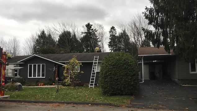Des pompiers observent les dégâts causés par un arbre qui s'est affaissé sur la toiture d'une résidence à Sherbrooke.