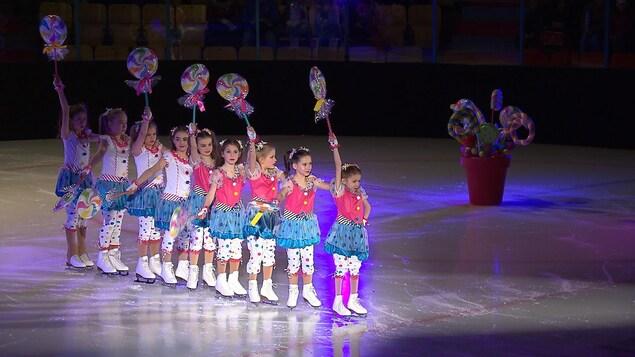 Des patineuses du Club de patinage artistique de Sept-Îles en costumes colorés présentent une chorégraphie.