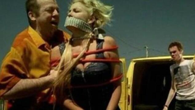 Le comédien Guy Nadon tient Véronique Cloutier, baillonnée et ligotée dans une scène du film.