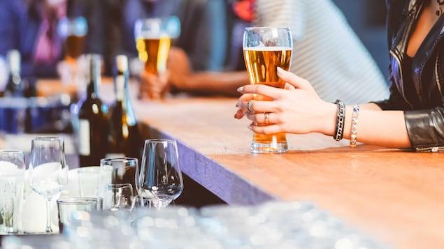 Une femme tient un verre de bière.