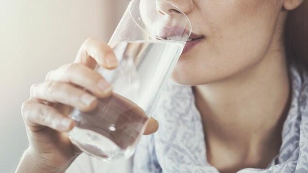 Une femme boit un verre d'eau.