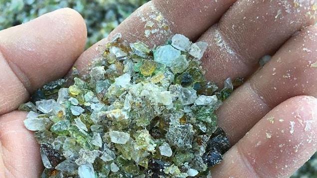 Main avec du verre recyclé.