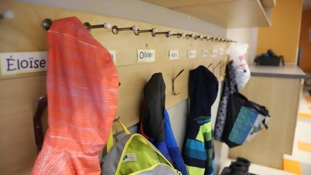 Des manteaux colorés s'alignent sur les crochets du vestiaire d'une garderie.