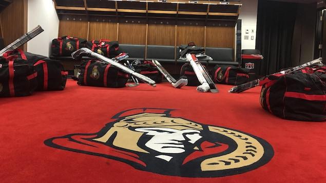 Un vestiaire de hockey avec des sacs et des bâtons au sol