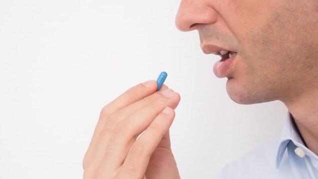 Un homme avale une pilule bleue.