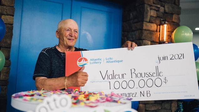 Viateur Rousselle tient un gros chèque d'un million.