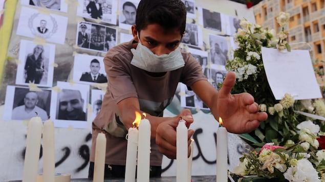 Un jeune homme allume des bougies devant des photos en noir et blanc de victimes des explosions.