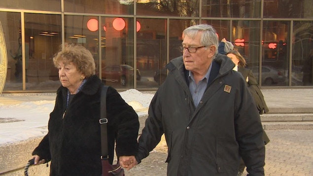 Un homme âgé et une femme âgée marchent denors en se tenant par la main. Ils ne regardent pas le photographe.