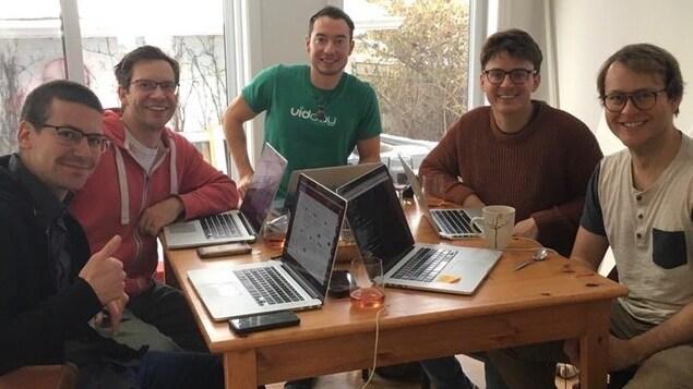Les membres de l'équipe de VidDay assis autour d'une table travaillent chacun à son ordinateur.