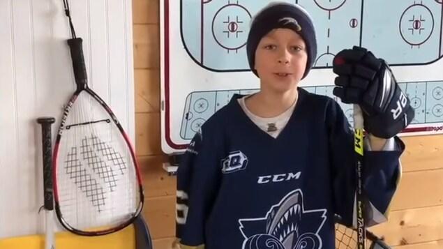 Un garçon, dans son uniforme de hockey, est appuyé sur son bâton, et s'adresse à la caméra.