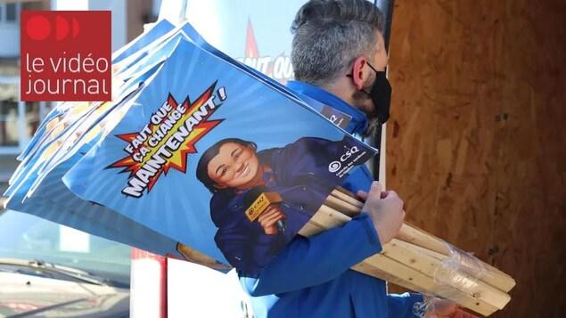 Un homme masqué transporte des pancartes syndicales.