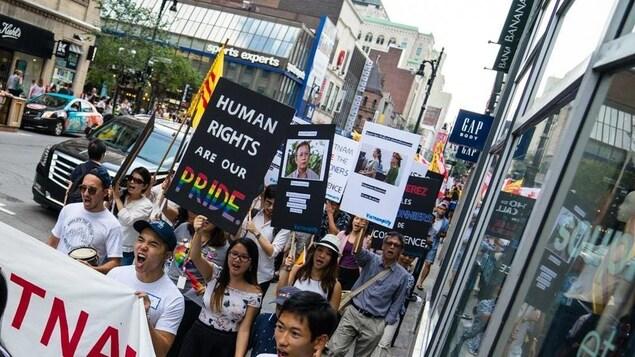 Les manifestants crient sur la rue Sainte-Catherine à Montréal lors de la première marche organisée par Vietnamplify, le 20 août 2017.