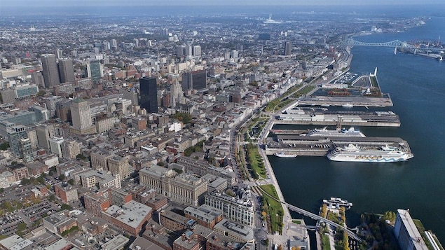 Une vue aérienne du Vieux-Port de Montréal avec le centre-ville et des bateaux de croisière à l'eau.