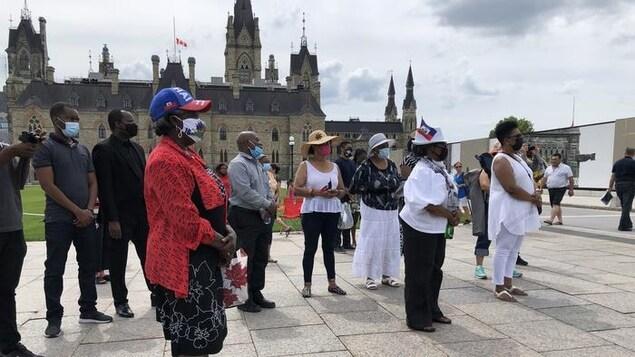 Des personnes sont réunies devant l'édifice du Parlement à Ottawa.