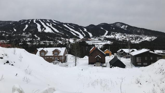 Plusieurs chalets devant un mont de ski.