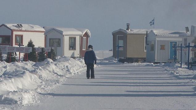Un marcheur arpente le sentier principal du village sur glace, entouré de maisonnettes.