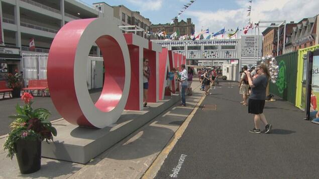 Des gens se font photographier devant des lettres géantes formant le mot OTTAWA.