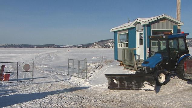 Le poste d'accueil du village de pêche blanche de Grande-Baie et un tracteur en bordure des glaces.