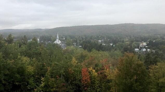 Le village de Saint-Élie-de-Caxton vu de haut, avec l'église au loin et de la forêt, l'automne.