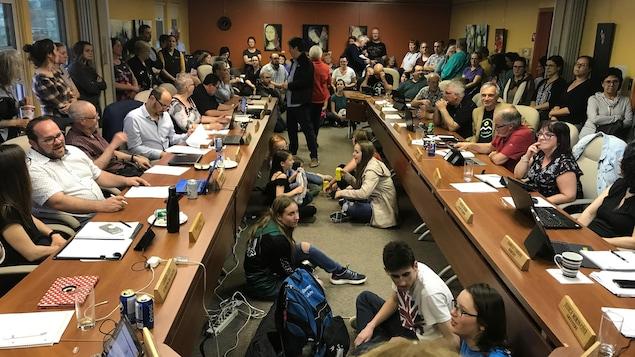 Des dizaines de personnes sont entassées dans la salle du conseil. Les membres du conseil sont assis à leurs places respectives, entourés d'adultes debout et des jeunes sont aussi assis par terre, par manque de chaises.