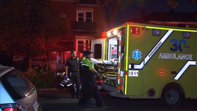 Des ambulanciers transportant un blessé dans leur véhicule.