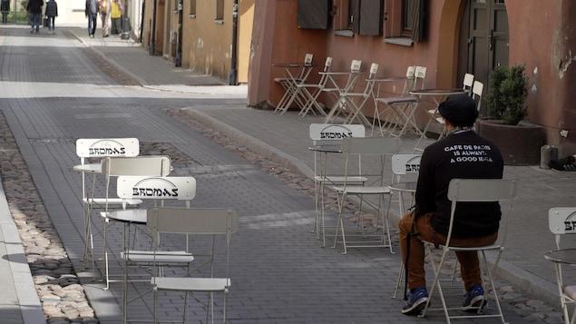 Un client assis à une table montée en plein rue.