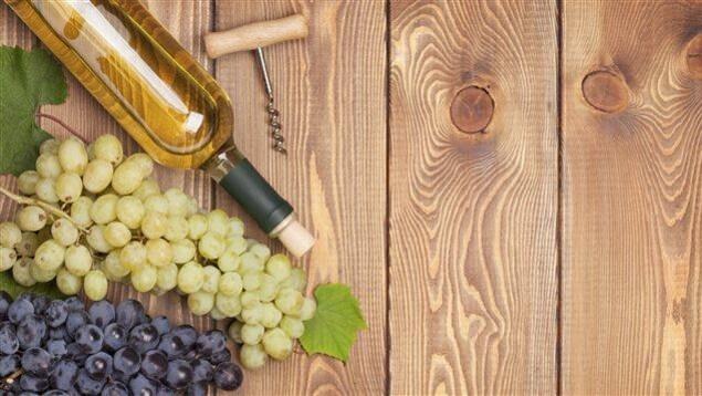 Des grappes de raisins, du vin blanc et un tire-bouchon.