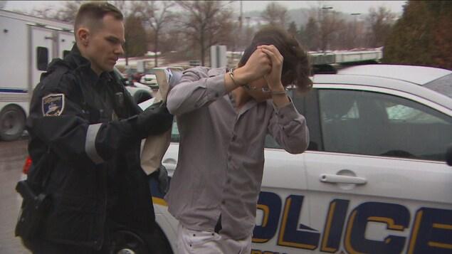 Un homme sort d'une voiture de police. Il a les mains menottées et se cache le visage.