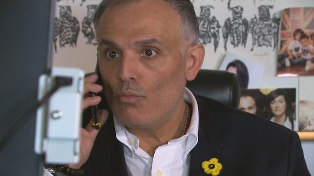 Il parle au téléphone devant son ordinateur dans son bureau.