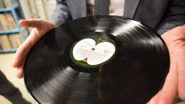 Une personne tient un disque des Beatles dans ses mains.