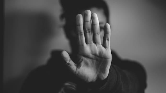 Une femme se défend, en montrant la main en signe «d'arrêt».