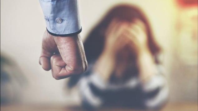 Un homme serrant le poing devant une femme avec les mains sur son visage.