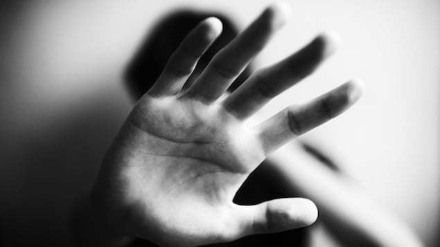 Une personne montre la paume de sa main pour se protéger.