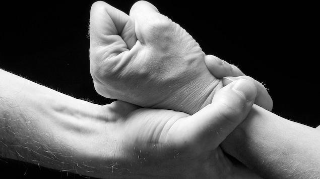 Gros plan sur une main d'homme qui serre le poignet d'une femme.