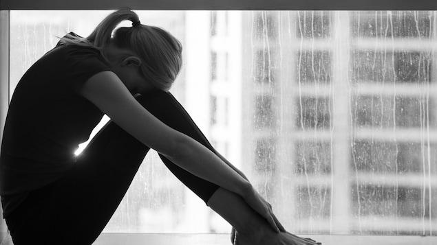 Une femme triste assise au bord d'une fenêtre.
