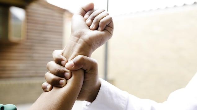 Quelqu'un agrippe le bras de quelqu'un d'autre.