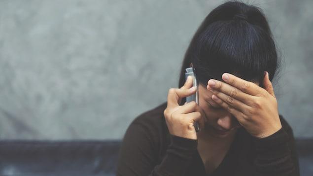 Une femme au téléphone, la tête baissée.